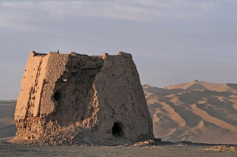 A Han dynasty-era rammed earth watchtower in Gansu province. The dunes of the Gobi desert stretch behind the ruins.
