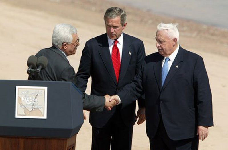Palestinian Authority leader Mahmoud Abbas, US President George W. Bush, and Israeli Prime Minister Ariel Sharon greet each other on stage behind a podium.