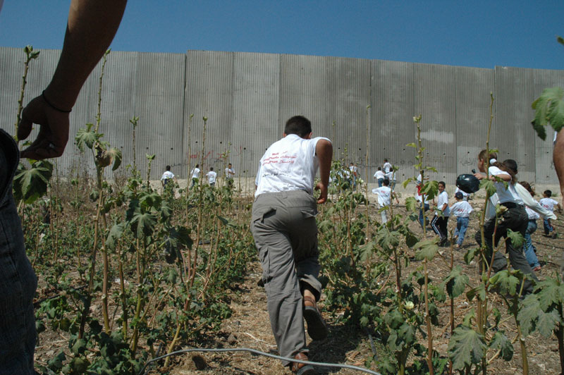 Palestinian children running through a field toward a large concrete wall.
