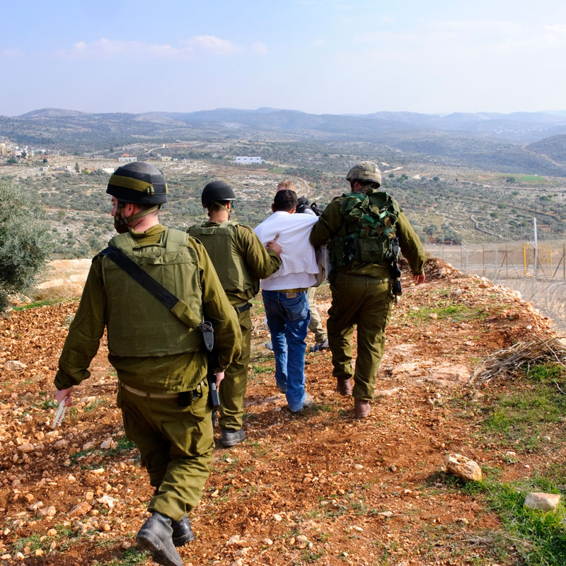 A group of soldiers are walking with a captured man in a white shirt.