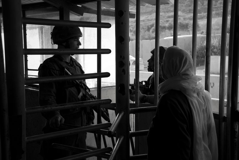 A woman speaking to two soldiers behind a metal fence.