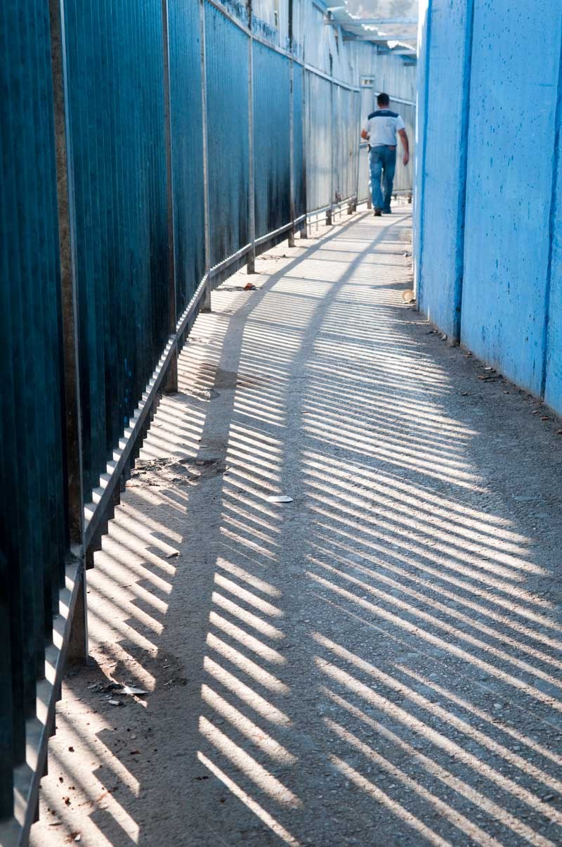 A man walking in a space between a metal fence and a concrete wall.